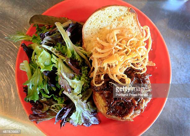 The pulled pork sandwich is served with onion strings a side salad with house vinaigrette dressing and a pickle For the Eat and Run review of the...