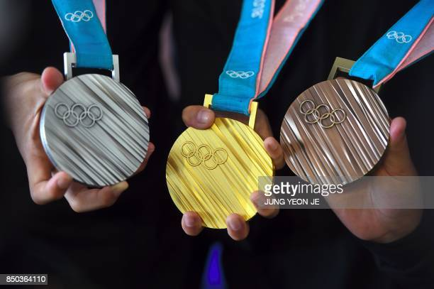The PyeongChang 2018 Olympic medals are displayed by young South Korean athletes during their unveiling at a ceremony in Seoul on September 21 2017...
