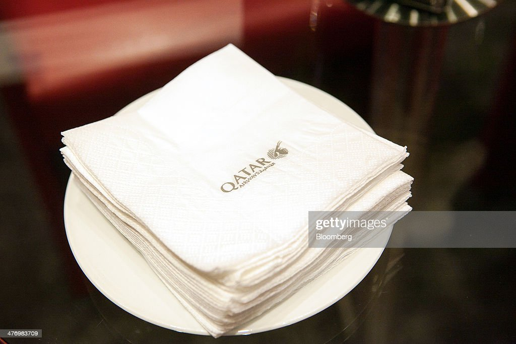 The Qatar Airways Ltd. logo sits on a pile of serviettes during the ITB travel fair at Messe Berlin exhibition center in Berlin, Germany, on Thursday, March 6, 2014. Al Baker said yesterday his company will be sticking with hard-wired inflight-entertainment systems. Photographer: Krisztian Bocsi/Bloomberg via Getty Images *** Local Caption