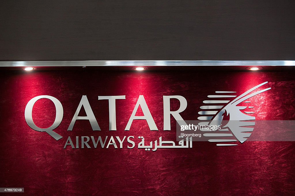 The Qatar Airways Ltd. logo sits on display at the company's stand during the ITB travel fair at Messe Berlin exhibition center in Berlin, Germany, on Thursday, March 6, 2014. Al Baker said yesterday his company will be sticking with hard-wired inflight-entertainment systems. Photographer: Krisztian Bocsi/Bloomberg via Getty Images