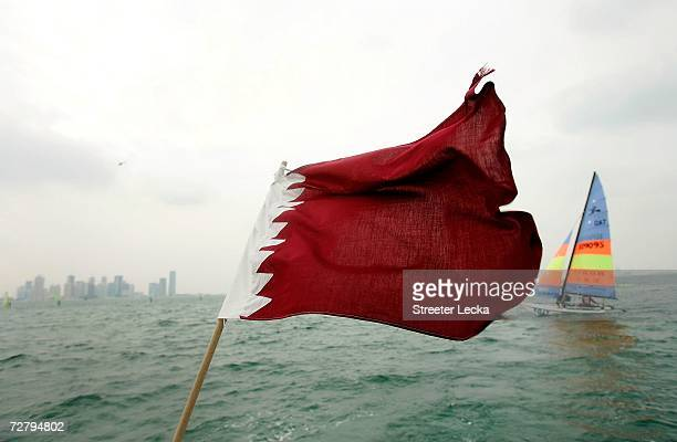 The Qatar Hobie 16 team sails towards the Doha skyline as the Qatari flag blows in the wind during the 15th Asian Games Doha 2006 at the Doha Sailing...