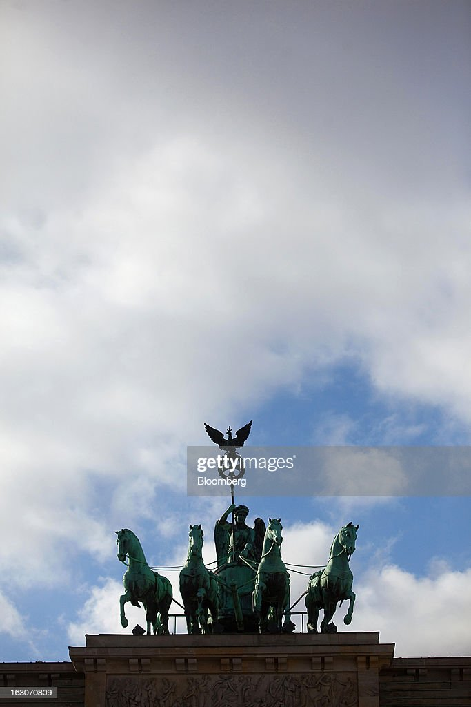 The Quadriga sculpture stands above the Brandenburg Gate in Berlin, Germany, on Sunday, March 3, 2013. Germany's 10-year government bonds advanced for a second day even before a report that economists said will show producer prices in the euro area increased for the first time in four months in January. Photographer: Krisztian Bocsi/Bloomberg via Getty Images