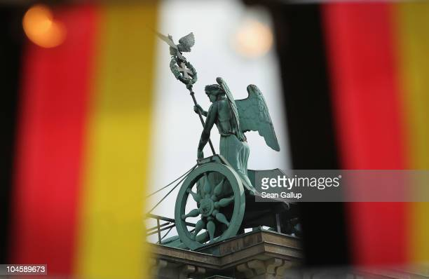 The Quadriga statue on top of the Brandenburg Gate is seen thru German flags at an outdoor kiosk set up for the upcoming unity celebration on October...