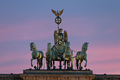 The Quadriga statue stands on top of the Brandenburg Gate at sunset on May 19 2015 in Berlin Germany Berlin is among Europe's major tourist and...
