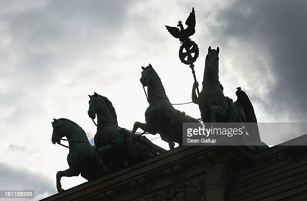 The Quadriga statue stands on top of the Brandenburg Gate silhouetted against dark clouds on September 19 2013 in Berlin Germany Germany faces...