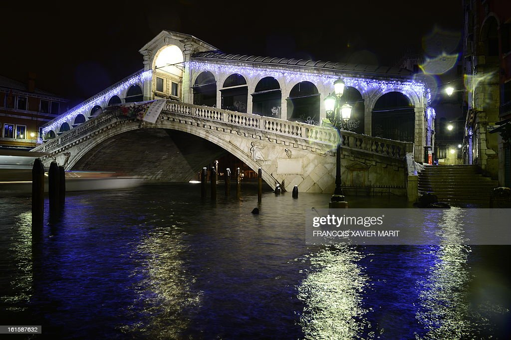 The quay is flooded near the Rialto bridge during an acqua-alta (high-water) late on February 11, 2013 in Venice. The 'acqua alta', a convergence of high tides and a strong sirocco, reached 143 centimetres around midnight.
