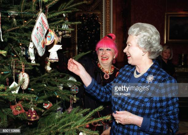 The Queen and fashion designer Zandra Rhodes admire Christmas decorations on the tree in the Picture Gallery at Buckingham Palace today after meeting...