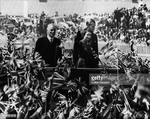 The Queen and the Duke of Edinburgh are cheered by a crowd of children waving flags at a picnic at Ferbury Park Racecourse Dunedin during their tour...