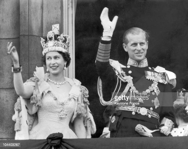 The Queen and the Duke of EDINBURGH wave from the famous balcony at Buckingham Palace to the vast crowds massed outside the Palace on June 2 1953...