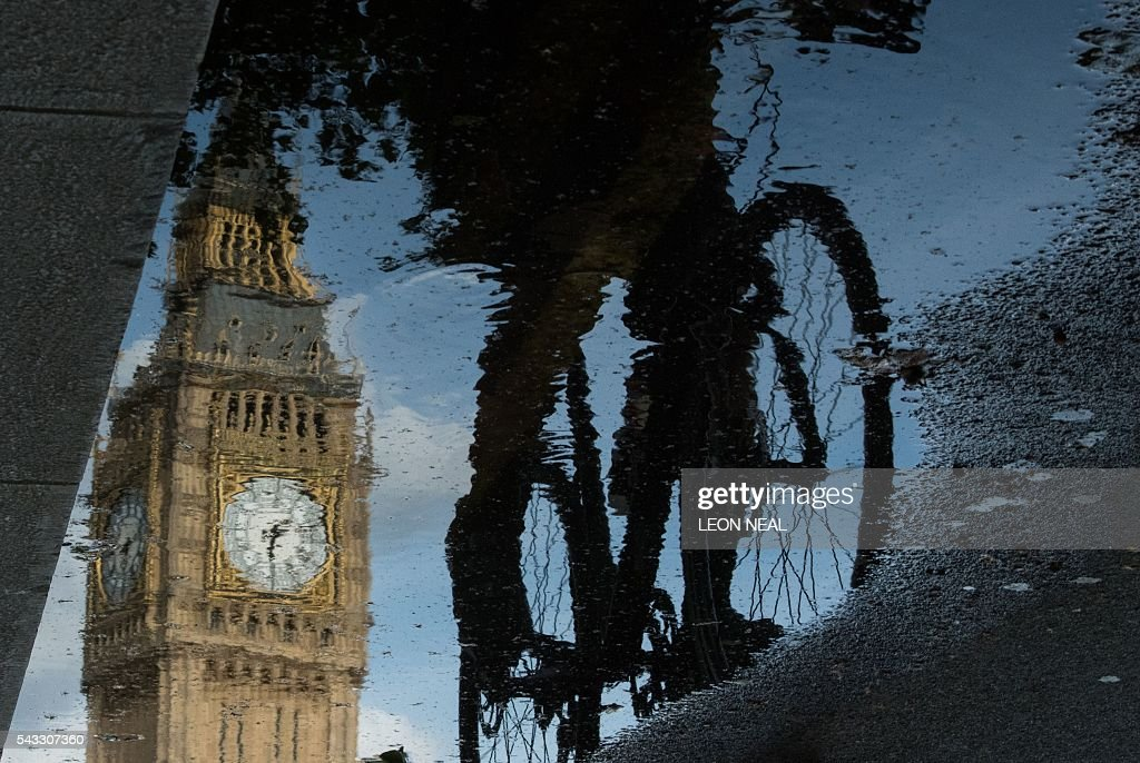 The Queen Elizabeth Tower (Big Ben) is reflected in a puddle as a cyclist rides by in London, on 27 June 2016. Britain began preparations to leave the European Union on Monday but said it would not be rushed into a quick exit, as markets plunged in the wake of a seismic referendum despite attempts to calm jitters. / AFP / Leon NEAL