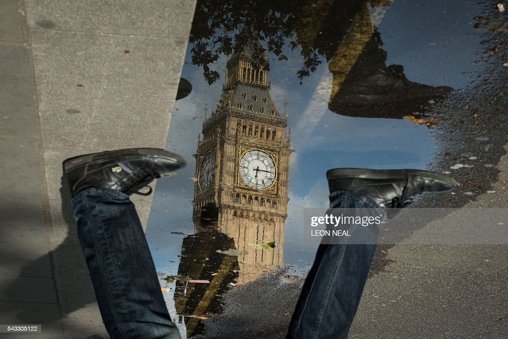 The Queen Elizabeth Tower (Big Ben) is reflected in a puddle as a man walks by in London, on 27 June 2016. Britain began preparations to leave the European Union on Monday but said it would not be rushed into a quick exit, as markets plunged in the wake of a seismic referendum despite attempts to calm jitters. / AFP / Leon NEAL