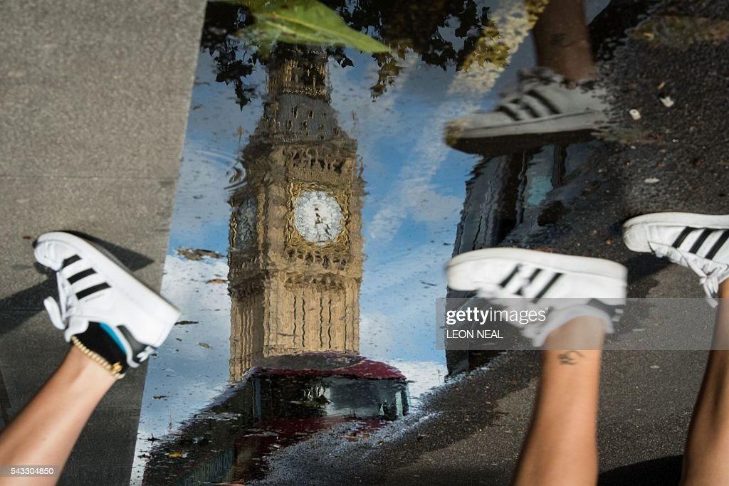 The Queen Elizabeth Tower (Big Ben) is reflected in a puddle as runners pass by in London, on 27 June 2016. Britain began preparations to leave the European Union on Monday but said it would not be rushed into a quick exit, as markets plunged in the wake of a seismic referendum despite attempts to calm jitters. / AFP / Leon NEAL