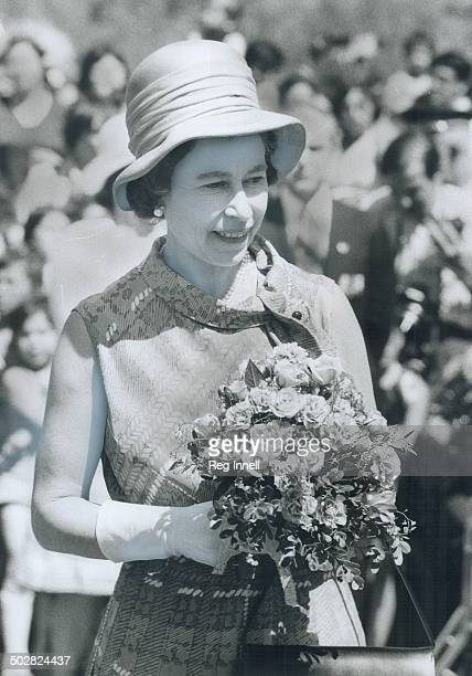The Queen holds a bouquet presented to her yesterday in Thunder Bay by 8yearold Trina Pelletier the daughter of Chief Leonard Pelletier of the Fort...