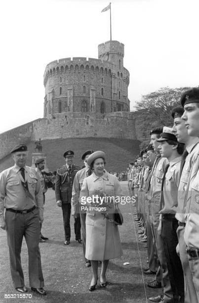 The Queen inspecting a parade of Queen's Scouts with Windsor Castle in the background when the scouts held their St George's Day parade there