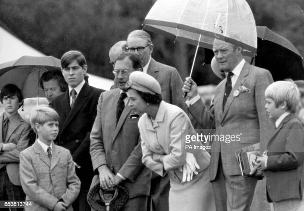 The Queen leans forward to speak to Prince Edward while being sheltered from the rain by the Duke of Wellington They were attending the annual Game...