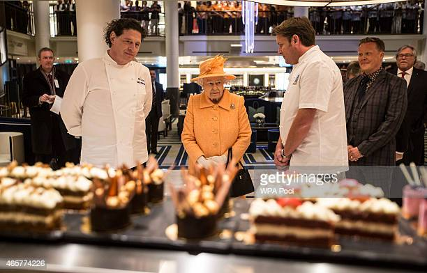 The Queen looks at cakes and sweets on the patisserie counter on board the new PO cruise liner 'Britannia' with chefs Marco Pierre White and James...
