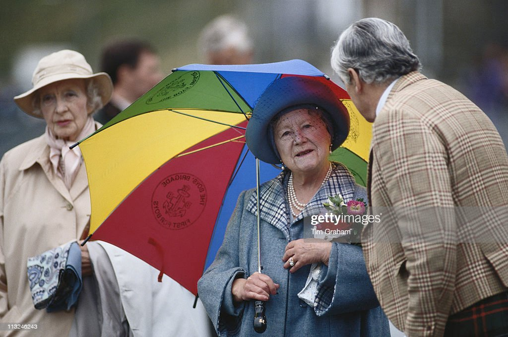 The Queen Mother (1900 - 2002) carrying a small bouquet of flowers and a multi-coloured umbrella, in Scrabster Harbour, Scrabster, Scotland, Great Britain, 15 August 1992. Ruth, Lady Fermoy (1908 – 1993), friend of the Queen Mother, and grandmother of Diana, Princess of Wales, stands to the left of the image, behind the Queen Mother.