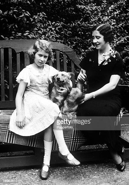 The Queen Mother pictured as The Duchess of York with her daughter Princess Elizabeth who holds a pet dog in the garden of their home 1936