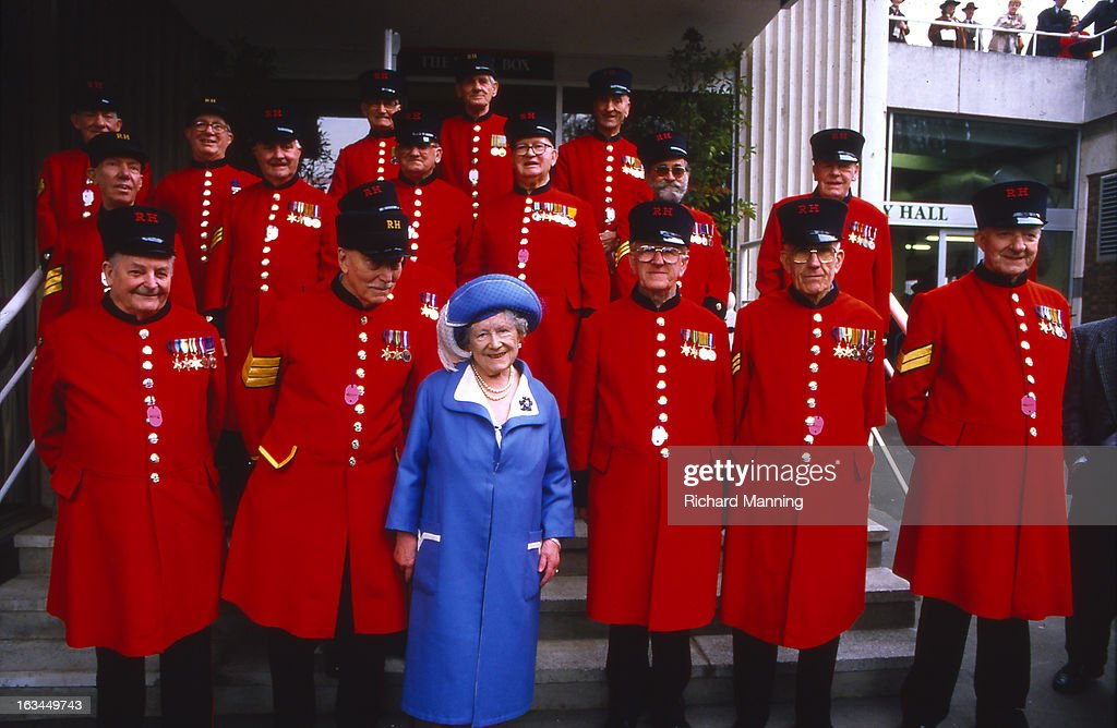 The Queen Mother poses with Chelsea Pensioners whilst attending the Grand Military Gold Cup, held annually at Sandown Park Racecourse in Esher, Surrey. It is a meeting point for the Military, in particularly for Cavalry Officers, with its origins in the days when mounted Cavalry Officers still rode to war.