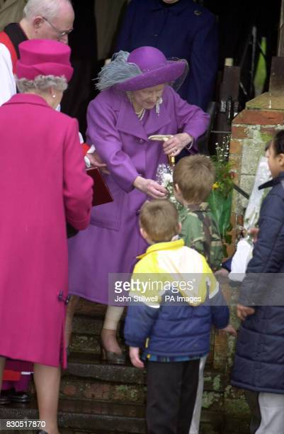 The Queen Mother receives flowers from a young wellwisher watched by Queen Elizabeth II after she and the Royal Family attended a Sunday church...