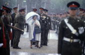 The Queen Mother sheltering from a sudden downpour of rain while reviewing the guard of honour of the Royal Anglian Regiment on May 10 1983 at...