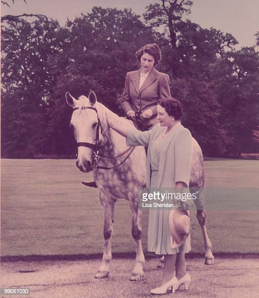 The Queen Mother standing next to Princess Elizabeth who is on a horse at the Royal Lodge in Windsor in England on 8 July 1946