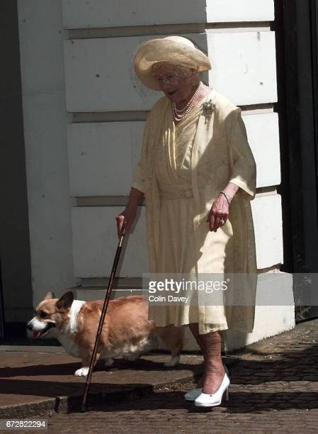 The Queen Mother walking with a corgi outside St James' Palace at an event to mark her 99th birthday London 4th September 1999