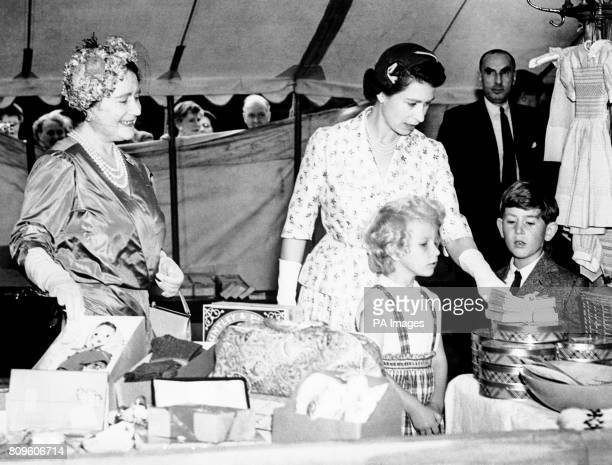 The Queen Mother watched as the Queen Princess Anne and Prince Charles examine goods on a stall at a sale of work at Abergeldy Castle near Balmoral...
