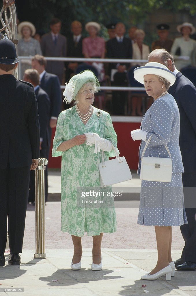 The Queen Mother (1900 - 2002), wearing a green and white floral print dress with a matching hat decorated wi|th pale green feathers and a net veil, and Queen Elizabeth II, wearing a blue suit with spots, designed by fashion designer Hardy Amies, at the opening of the Queen Elizabeth Gate in Hyde Park, London, England, Great Britain, 6 July 1993.