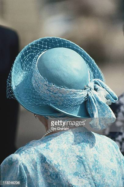 The Queen Mother with her back to the camera wearing a blue and white outfit with a blue hat on the occasion of her 87th birthday in London England...
