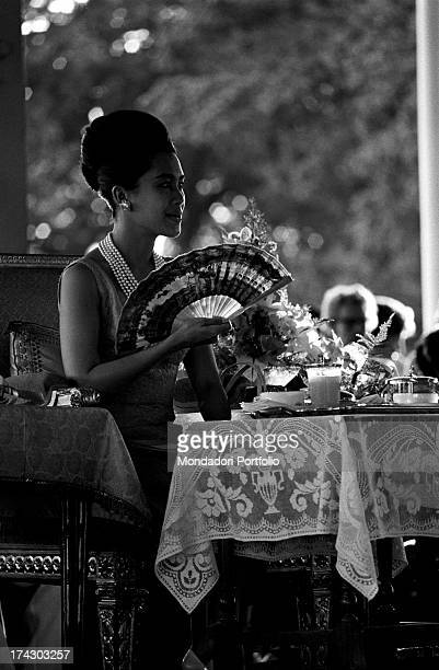 The Queen of Thailand Sirikit sitting at a table and clapping during a fashion show Bangkok 1965