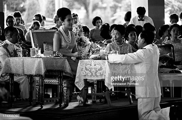 The Queen of Thailand Sirikit sitting at a table and waving her fan during an official ceremony during a fashion show Bangkok 1965