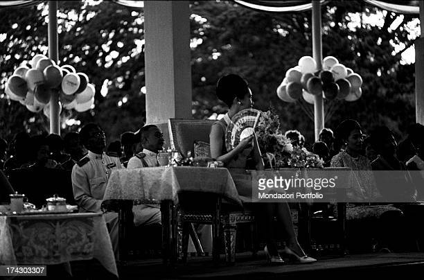 The Queen of Thailand Sirikit watching at a model walking down the catwalk during a fashion show Bangkok 1965