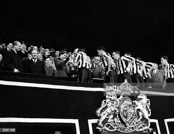 The Queen presents the FA Cup to the Captain of the winning Newcastle United side after their 31 victory over Manchester City at Wembley The Duke of...