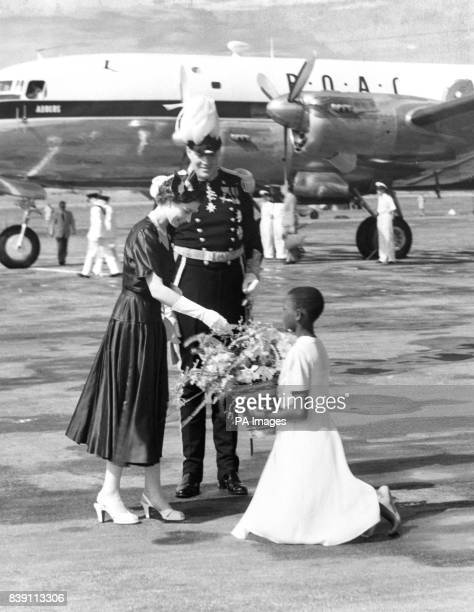 The Queen receives a basket of flowers from 12yearold Beata Kabasaindi on arrival at Entebbe Uganda looking on is Sir Andrew Cohen Governor of Uganda