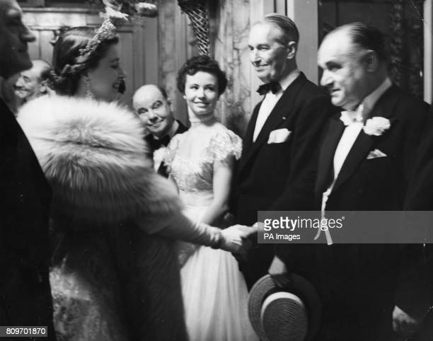 The Queen smiles as she shakes hands with Beniamino Gigli the Italian tenor as France's Maurice Chevalier straw hat in hand American dancer Nanci...