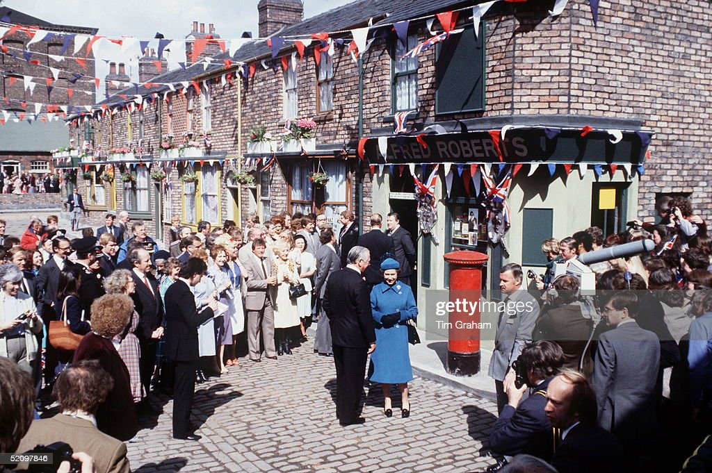 The Queen Visiting The Television Set Of 'coronation Street' In Manchester. Characters From The Series, Including Annie Walker, Bet Lynch And Mike Baldwin, Gather To See The Queen During Her Visit. At Left At Front Of Crowd With His Hands Together In Front Of Him Is Commander Mike Trestrail The Queens Police Bodyguard At The Time