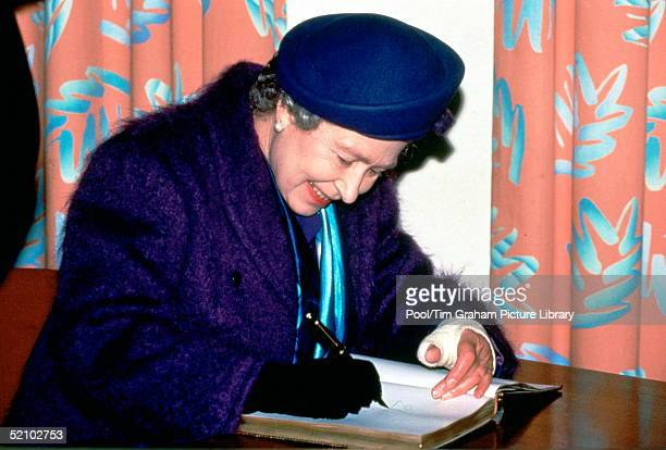 The Queen With A Fractured Wrist In A Bandage Signing Her Name In A Visitors Book During A Visit To Mount Vernon Hospital