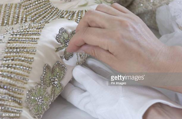 The Queen's Coronation dress of white satin is prepared for the Summer Opening of Buckingham Palace's State Rooms by senior textile conservator Janet...