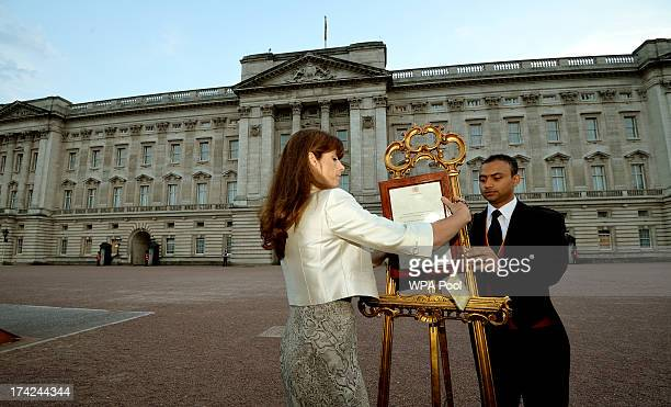 The Queen's Press Secretary Ailsa Anderson with Badar Azim a footman place the announcement on the easel which stands in the Forecourt of Buckingham...