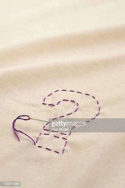 The question mark sewn with a thread