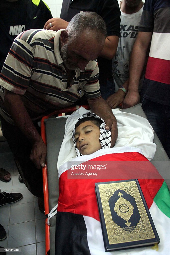 The Quran, the holy book of the Islam, is placed on 9-year-old Khalil al-Anati's body, wrapped in a Palestinian flag, in Hebron National hospital in West Bank on August 10, 2014. Anati, shot dead by Israeli troops during clashes in the south of the occupied West Bank, arrived in Hebron national hospital in a serious condition after being shot in the pelvis before succumbing to his wounds shortly later, a medical source at the hospital said.