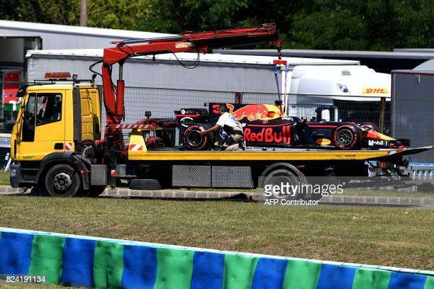 The racing car of Red Bull's Australian driver Daniel Ricciardo is towed away during a free practice session at the Hungaroring racing circuit in...