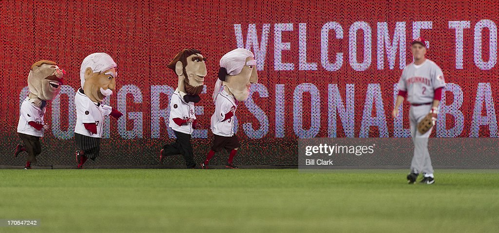 The Racing Presidents run along the outfield fence behind Rep. Brad Wenstrup, R-Ohio, during the 52nd annual Congressional Baseball Game at national Stadium in Washington on Thursday, June 13, 2013.