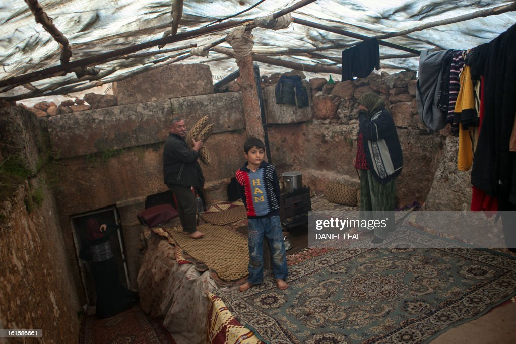 The Radwan family are seen in the living area of their make shift home set-up in the ruins of an ancient building in the old Roman city of Serjilla, in northwestern Syria, on February 11, 2013, after fleeing the fighting between rebel forces and pro-government troops in the town of Kfar Nubul, in the northwestern province of Idlib.