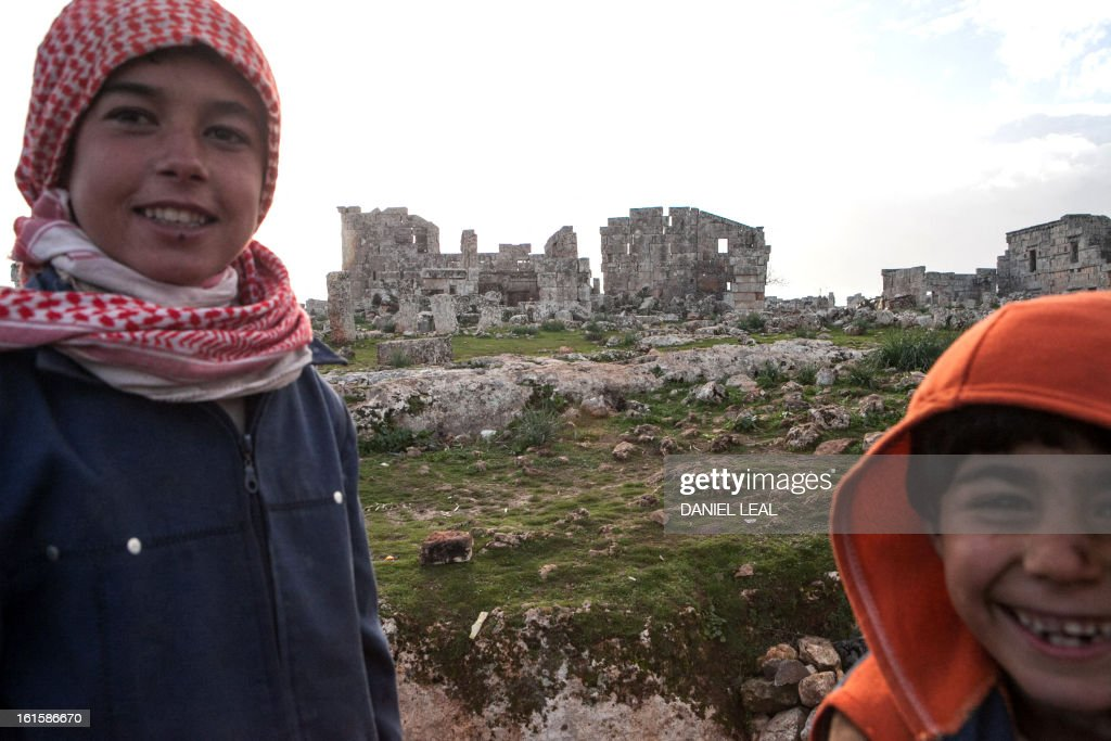The Radwan family children are seen in the grounds of the ancient Roman city of Serjilla, in northwestern Syria, where their family set up their home on February 11, 2013, after fleeing the fighting between rebel forces and pro-government troops in the town of Kfar Nubul, in the northwestern province of Idlib.