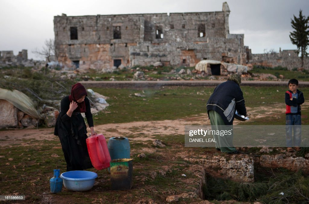 The Radwan family clean their few dishes in front of an ancient building in the old Roman city of Serjilla, in northwestern Syria, where they set up their home in the ruins on February 11, 2013, after fleeing the fighting between rebel forces and pro-government troops in the town of Kfar Nubul, in the northwestern province of Idlib.