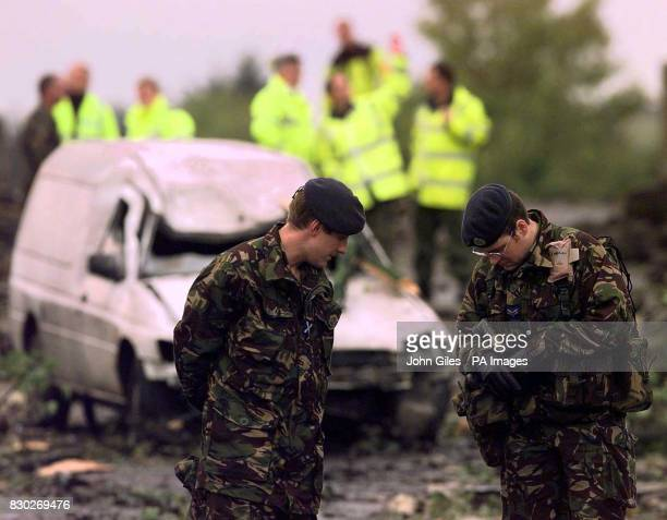 The RAF Police and Air Safety experts examine the wreckage of a RAF Hawk training jet from 100 Squadron which struck a railway bridge and exploded on...