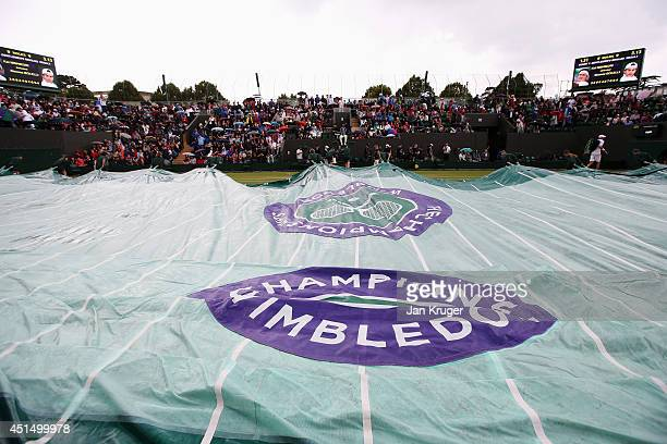 The rain covers are pulled onto court three as rain suspends play on day seven of the Wimbledon Lawn Tennis Championships at the All England Lawn...