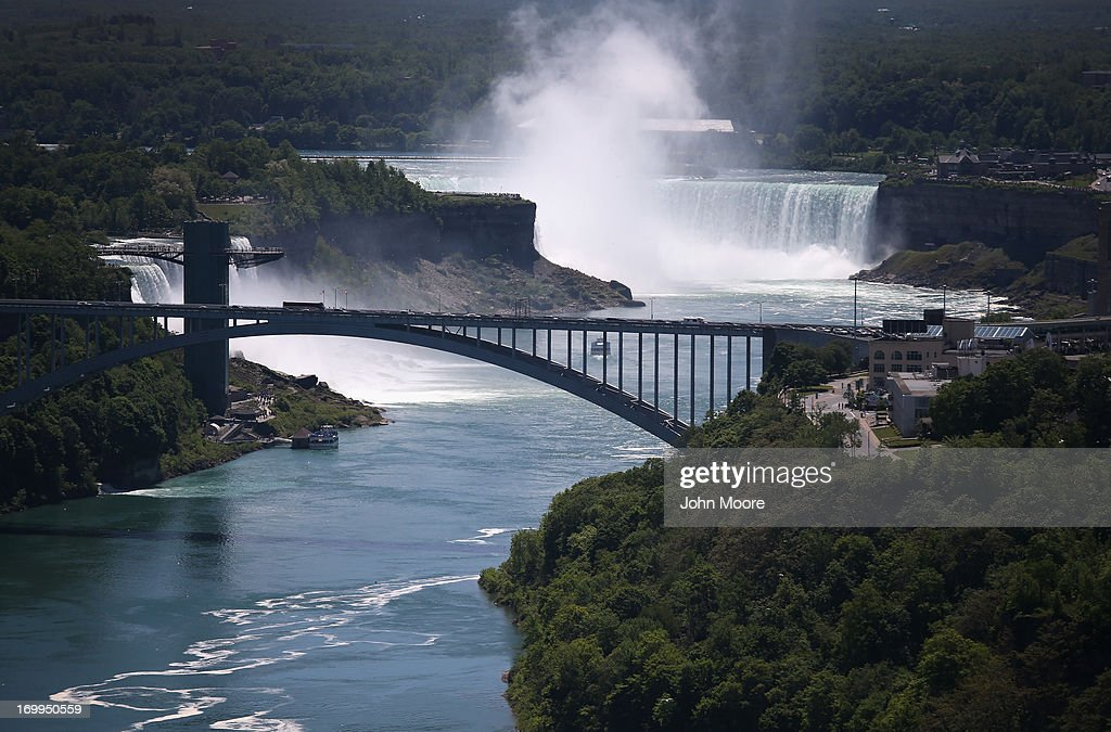 The Rainbow Bridge crosses from the United States (L), into Canada near the Niagara Falls on June 4, 2013 at Niagara Falls, New York. The falls, which have a combined highest flow rate of any waterfalls in the world, stradle the U.S.-Canada border, on the the Niagara River, which drains Lake Erie into Lake Ontario. The falls, visited by millions of tourists on each side of the border, are also a major source of hydroelectric power for the region. The aerial view was seen from a helicopter flown by the U.S. Office of Air and Marine, (OAM), which monitors and patrols the U.S. northern border with Canana.